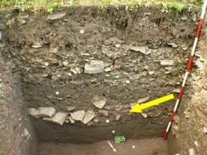 obr. 3 - Chrudim, Lázeňská ulice. Žlutá šipka označuje rozvalenou čelní kamennou plentu raně středověkého valu.