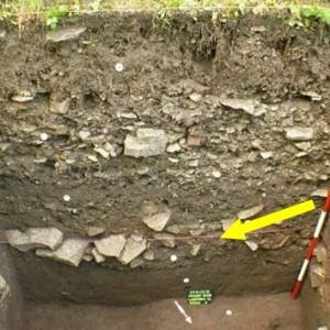 obr. 3 – Chrudim, Lázeňská ulice. Žlutá šipka označuje rozvalenou čelní kamennou plentu raně středověkého valu.